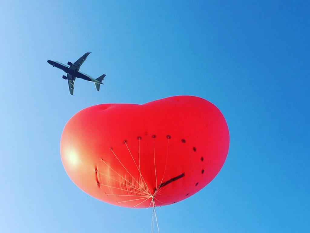 Aeroplane flying above inflatable heart